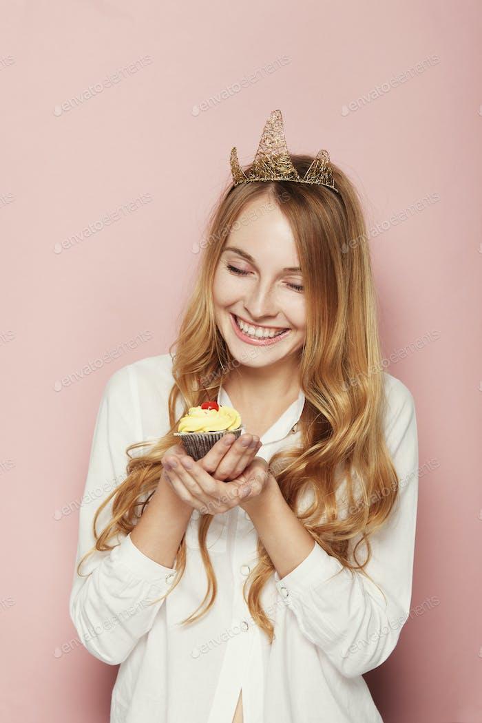 Mujer sonriente, con una corona, la celebración de una magdalena de cumpleaños