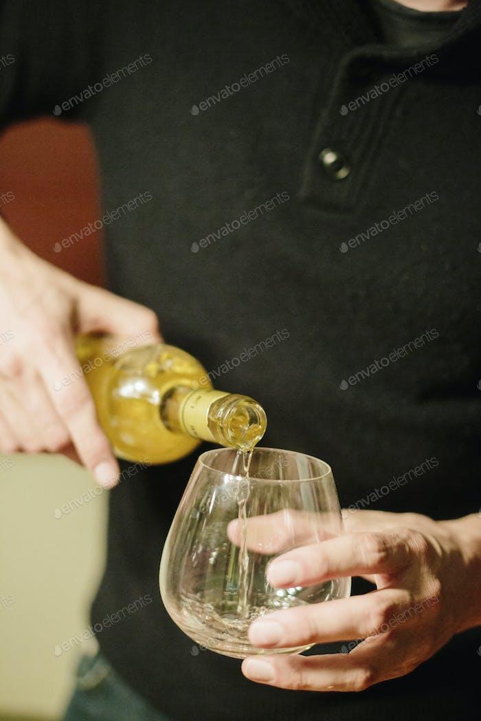 Ein Mann, der ein Glas Spirituosen in ein Glas gießt.