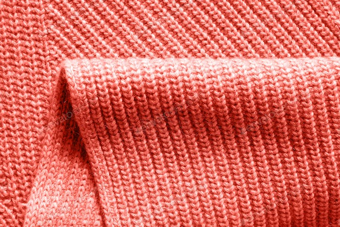 Warm wool knitted clothes background with fold in a trendy color of the year 2019 Living Coral
