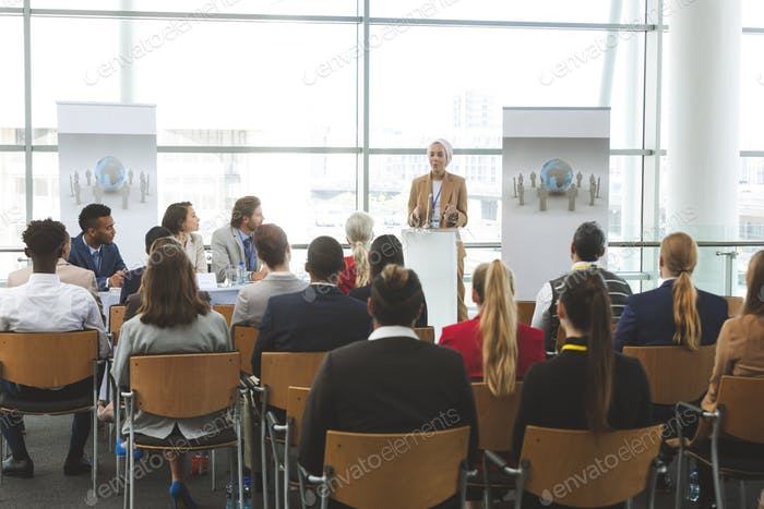 Female speaker speaking in a business seminar in modern office building