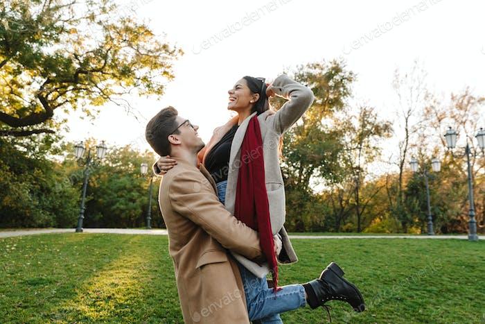 Bild von stilvollen jungen Mann tragen Frau in den Händen und lächelnd im Park