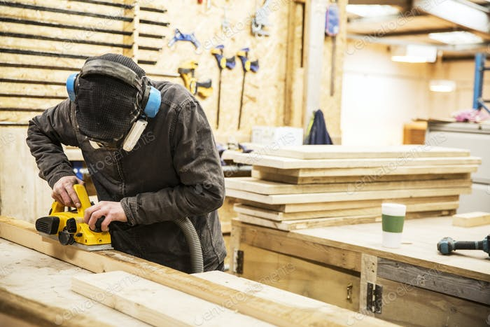 Man wearing ear protectors, protective goggles and dust mask standing in a warehouse, sanding planks