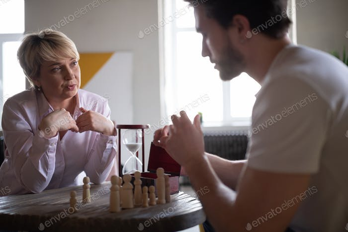 Mature psychologist speaking to aggressive patient