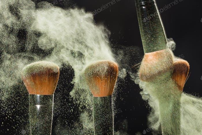 Make-up, Schönheit, mineralische kosmetische Konzept - Pinsel Bürsten ein Pulver von einem anderen Pinsel über die