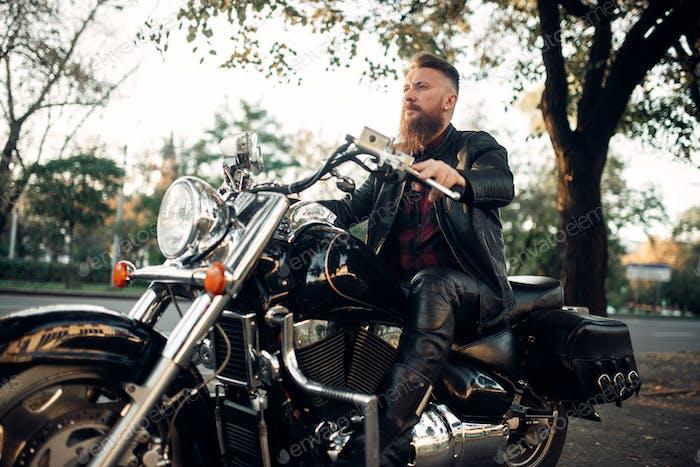 Biker sitting on a motorcycle leaning on a helmet