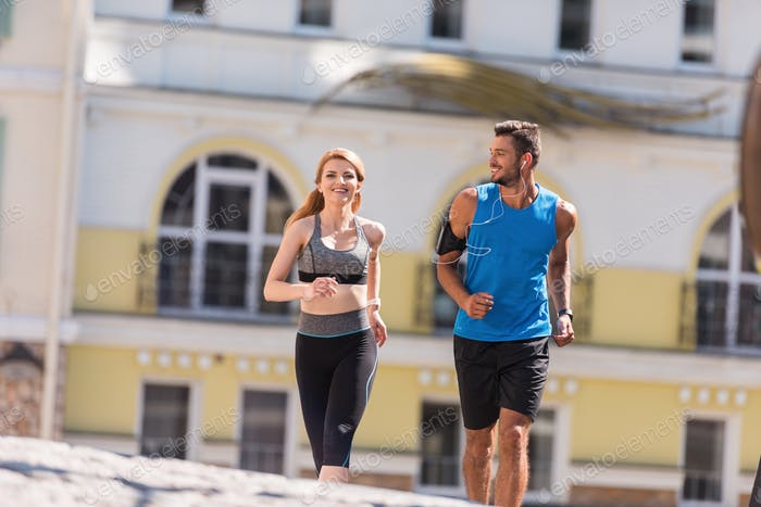 athletic sportswoman and sportsman jogging in city at daytime