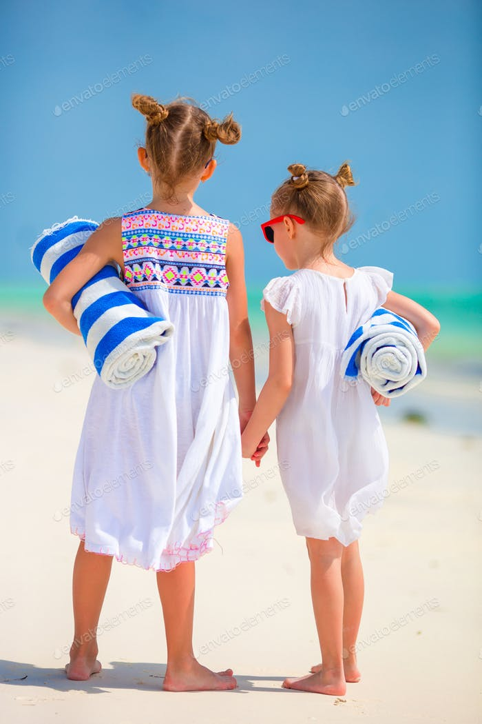 Adorable little girls with towels at tropical beach