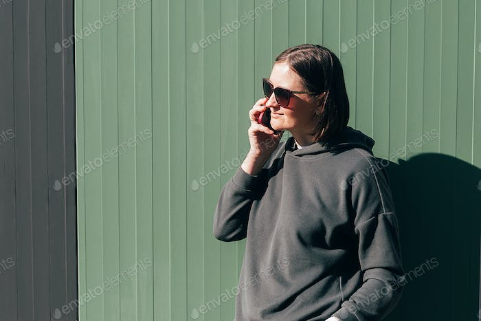 Portrait young woman in a green sweatshirt and glasses talking on phone over green background