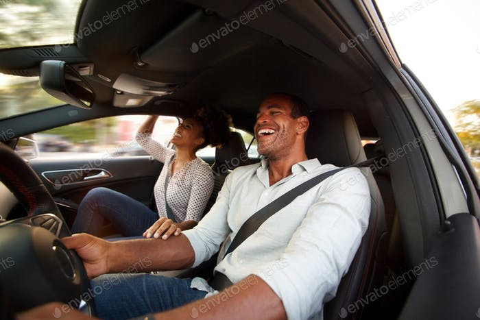 Close up man and woman smiling and sitting together in automobil