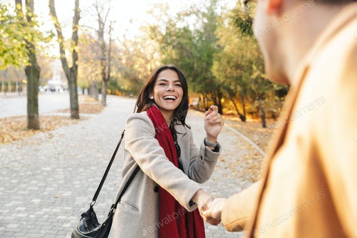 Porträt von jungen glücklichen Paar lächelnd und Hand halten beim Gehen im Herbst Park