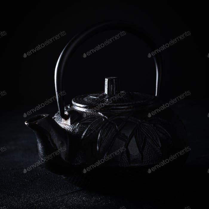 Teekanne aus schwarzem Eisen über dunklem Hintergrund