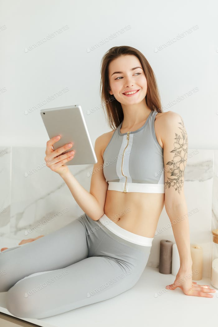 Young lady in sporty top and leggings sitting on kitchen with tablet cheerfully looking aside