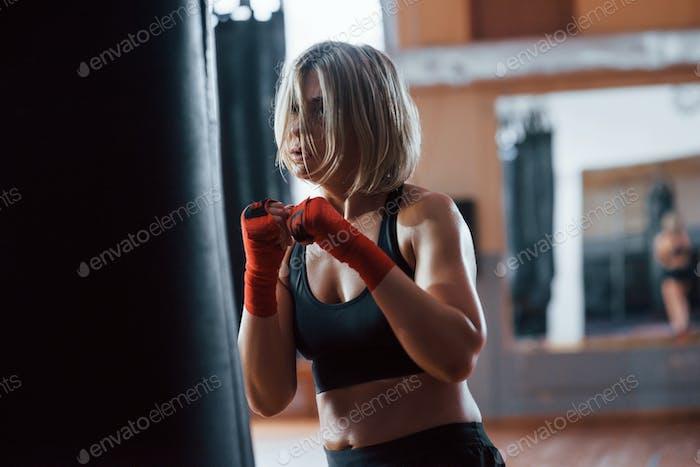 Schweres Atmen. Weiblicher Boxer stanzt den Sack. Blonde haben Bewegung im Fitnessstudio