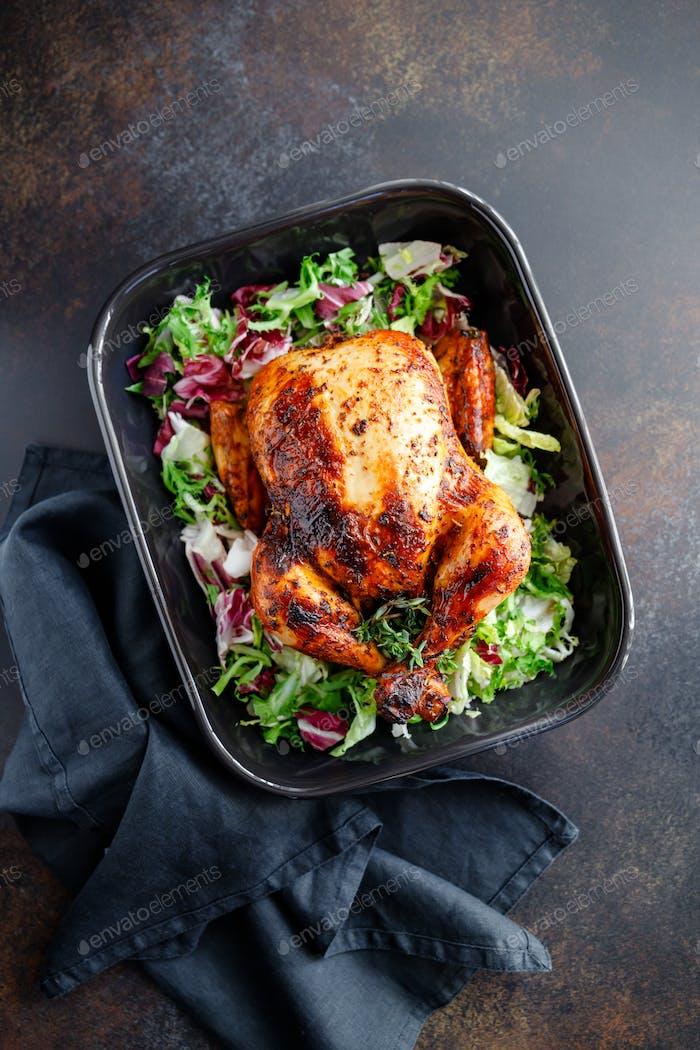Vista superior de pollo asado entero con ensalada fresca en plato negro.