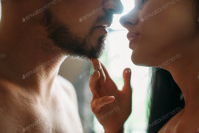 Man and woman kissing against a window, erotica