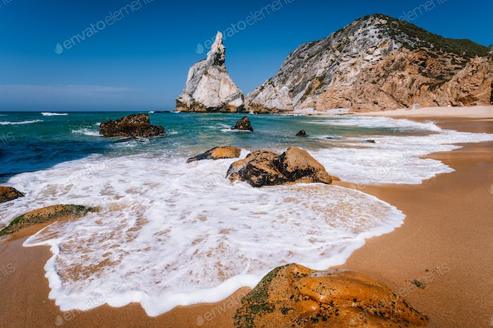 Portugal Ursa Beach at atlantic ocean coast. Foamy wave at sandy beach with surreal jugged rock in