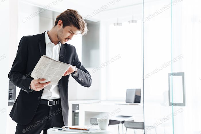 Photo of serious businessman reading newspaper and looking at wristwatch