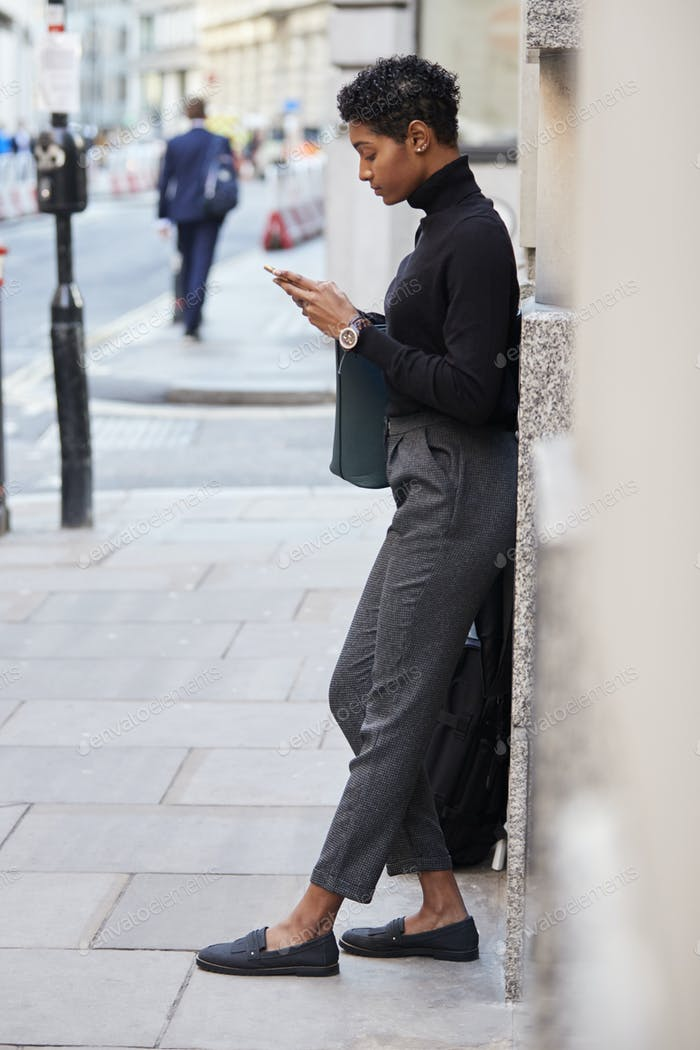 Young adult woman leaning on a wall in a London street using her smartphone, full length