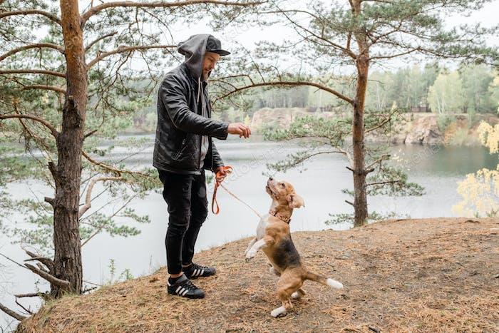 Junger Mann geben etwas Leckeres zu niedlichen reinrassigen Beagle Welpen während der Kälte