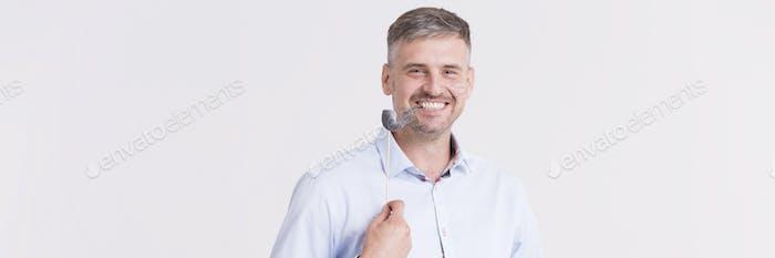 Lächelnder Mann mit Papierpfeife
