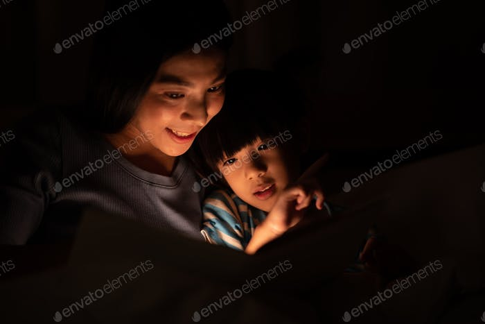 Happy mother and her little daughter reading book on the bed with cozy night