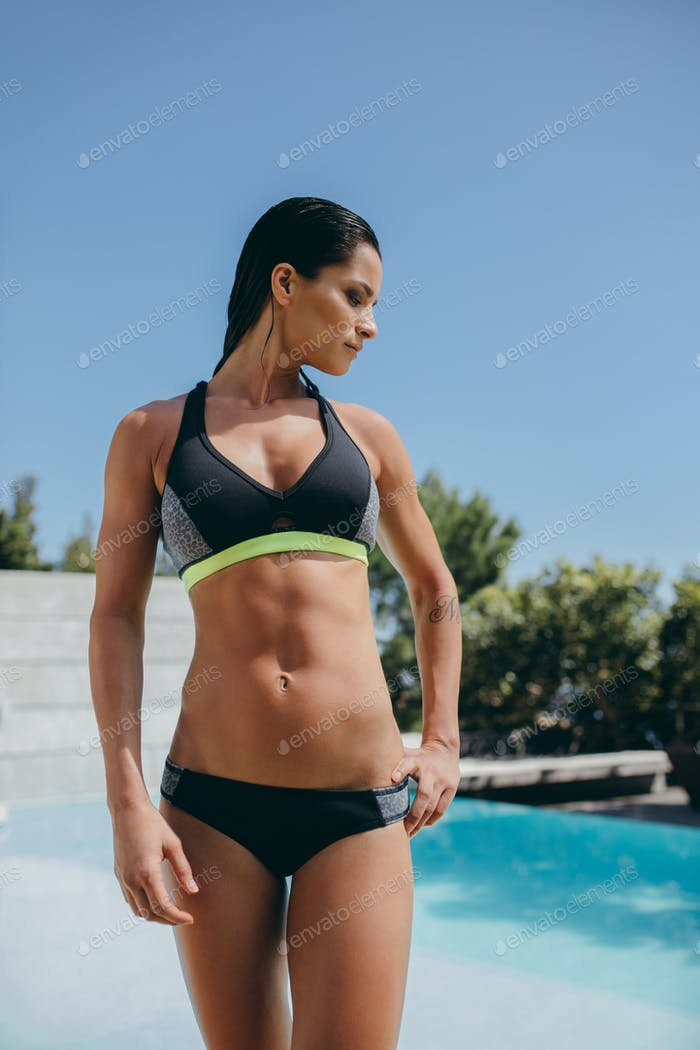 Female model in sports wear standing by the poolside