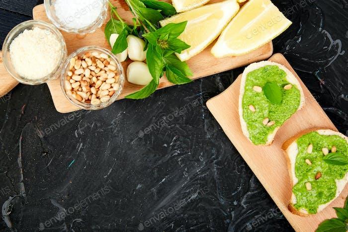 Bruschetta with pesto sauce, parmesan cheese and fresh basil