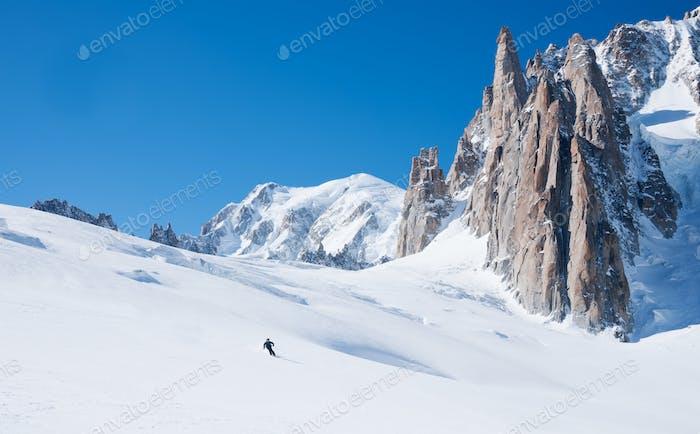 Skier goes downhill on a alpine glacier
