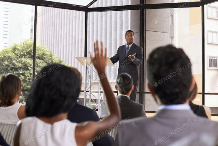 Black businessman giving seminar takes audience questions