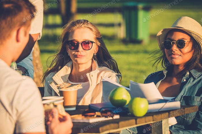Multi-ethnic friends drinking coffee and chatting in a park