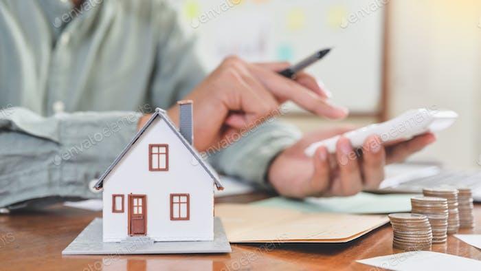 Modellhäuser und Münzen mit Menschen mit dem Rechner auf dem Hintergrund, Hauskostenkonzept.