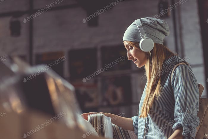 Young girl with headphones in a music store