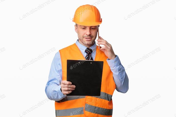 Repairman Worker Talking On Cellphone Holding Folder Standing In Studio