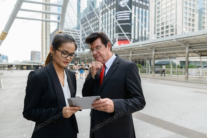 Mature businessman and young Asian businesswoman using digital tablet together in the city
