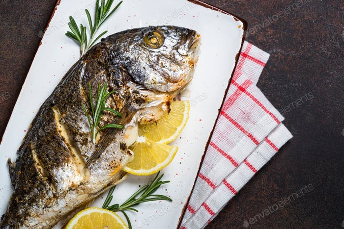 Baked dorado fish with lemon and rosemary.