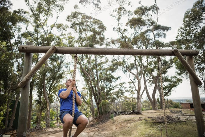 Fit man climbing down the rope during obstacle course