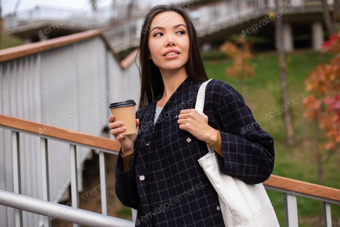 Young attractive casual woman in coat with coffee to go thoughtfully looking away in city park