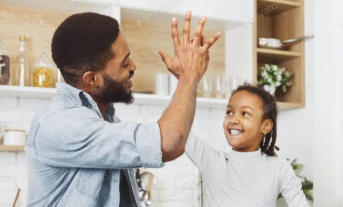 Cute girl and handsome dad giving high five in kitchen
