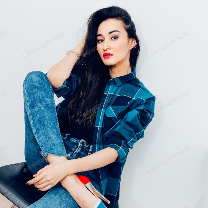 Beautiful brunette model with long hair in checkered shirt. Casu