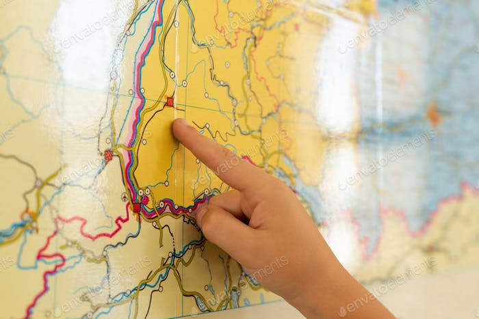 Close-up of Caucasian boy pointing his finger on world map in a classroom at elementary school