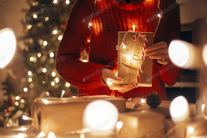 Girl wrapping christmas presents in lights in evening festive room
