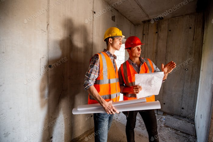 Construction manager and engineer dressed in orange work vests and helmets work with construction