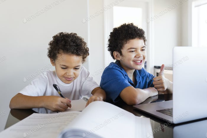Brothers doing homework at home during the new normal