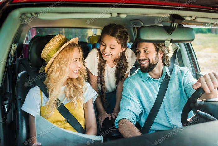 smiling parents and daughter traveling by car with map