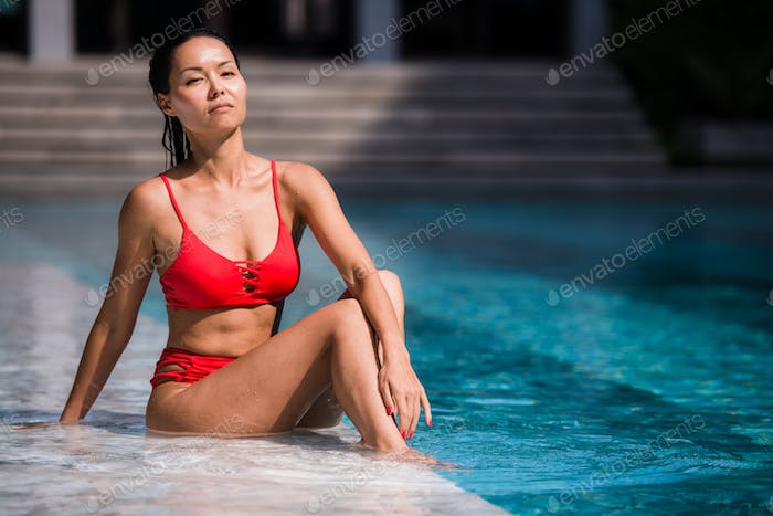 Elegant sexy woman in bikini on sun-tanned slim and shapely body posing near swimming pool. Gorgeous