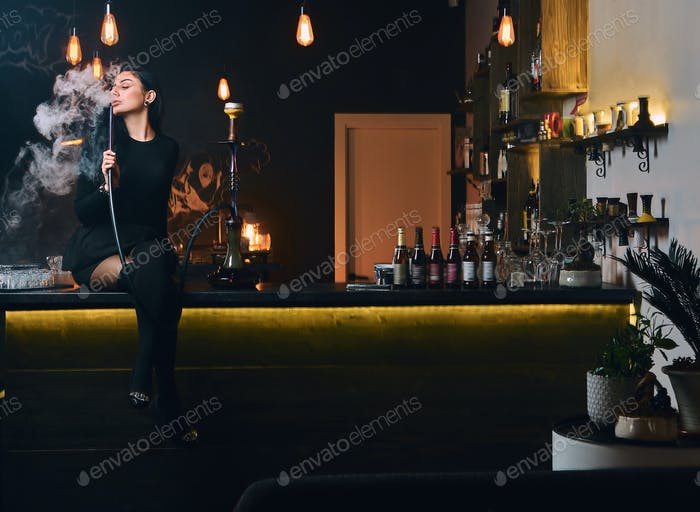 Seductive brunette girl in black clothes in a hookah