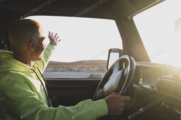one man driving his car looking and enjoying the beautiful landscape sunset