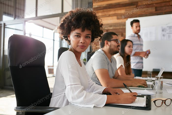 Confident businesswoman sitting at a business presentation