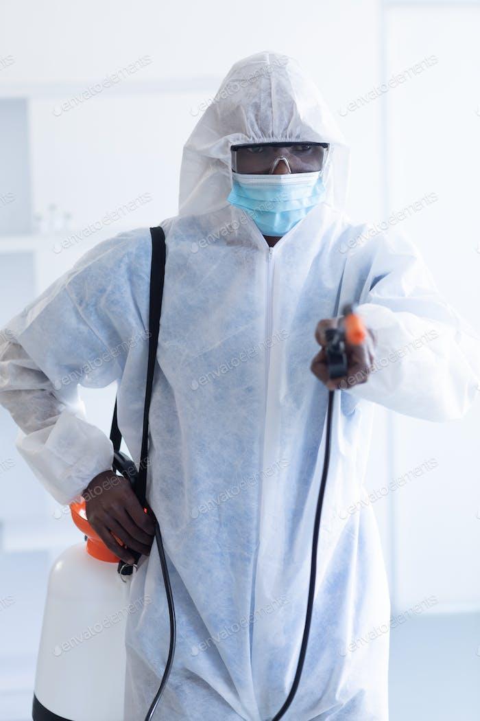 Gesundheitsarbeiter mit Schutzkleidung, die mit Desinfektionsmittel gereinigt wird