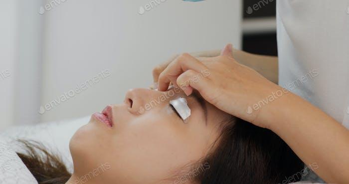 Woman perm eyelashes at beauty salon